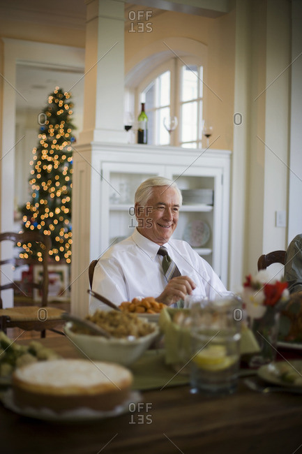 Senior man sitting at the dining table for Christmas dinner.