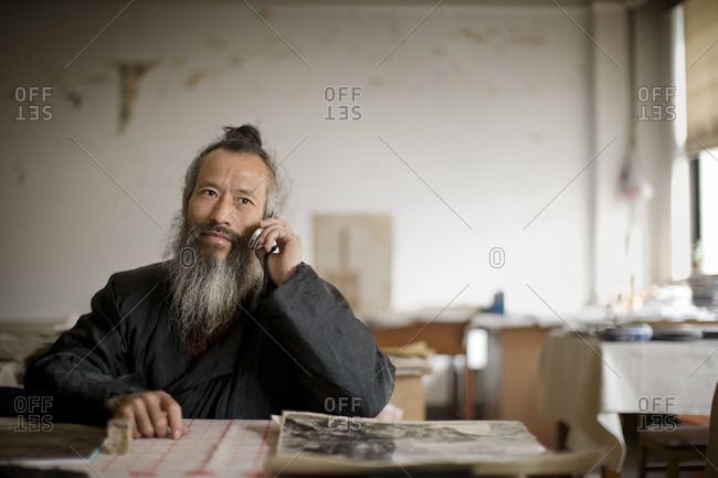 Artist sitting at his desk in his studio.