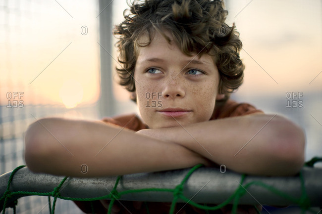 Young boy leaning on a goal post.