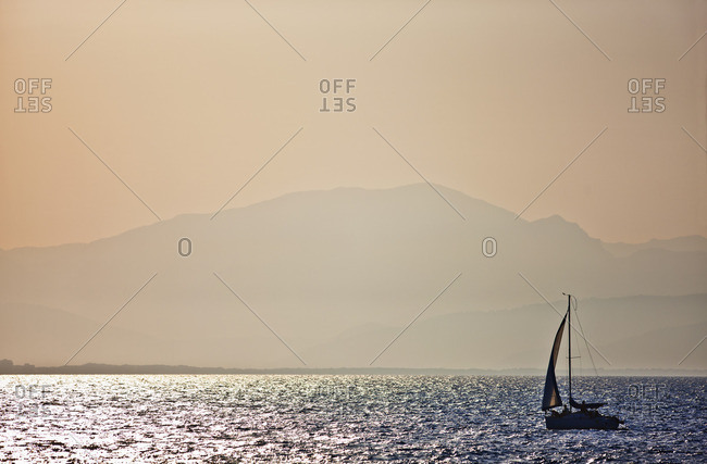 Sailboat on a calm ocean at sunset.