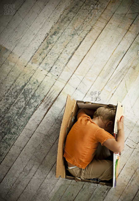 Young boy playing hide and seek in a cardboard box.