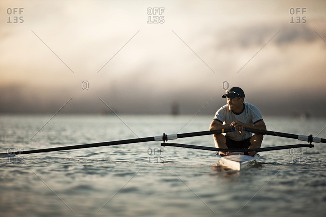 Man rowing in a single scull boat.