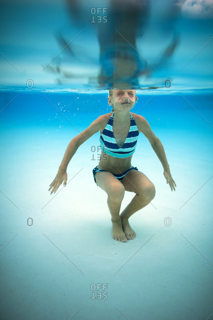 Young girl swimming underwater in a pool.