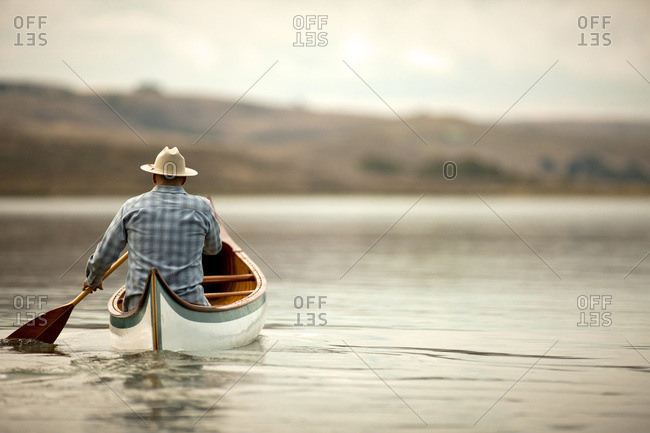 Man canoeing on a tranquil lake.