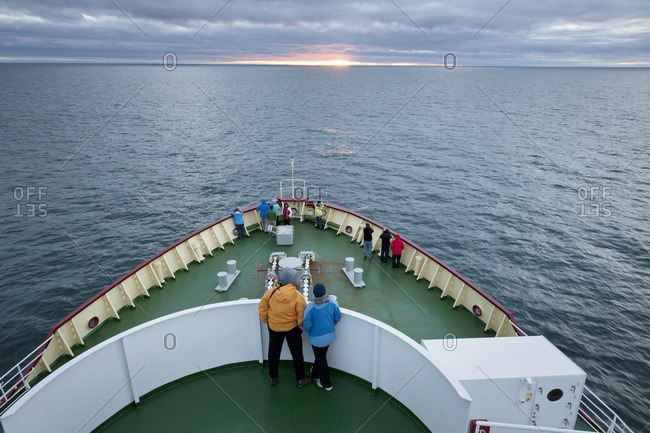 Passengers standing on the bow of a ship at sunset.
