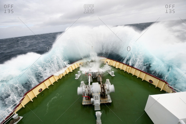 Bow of a ship coursing through powerful waves.