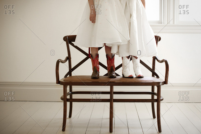 Two young girls standing on a bench, wearing dresses and cowboy boots.