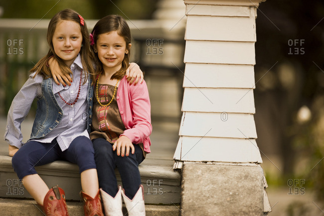 Two young girls in cowboy boots sitting on their deck.