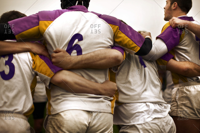 Rugby players in a team huddle.