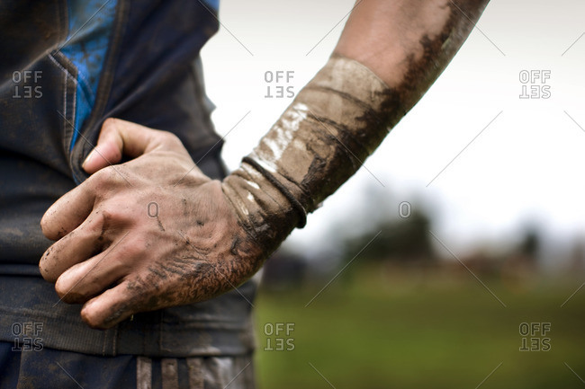 Dirt and mud covering a rugby player's hand.