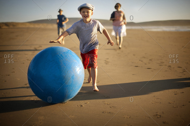 Young boy chasing a ball along the beach, with his parents following behind him.