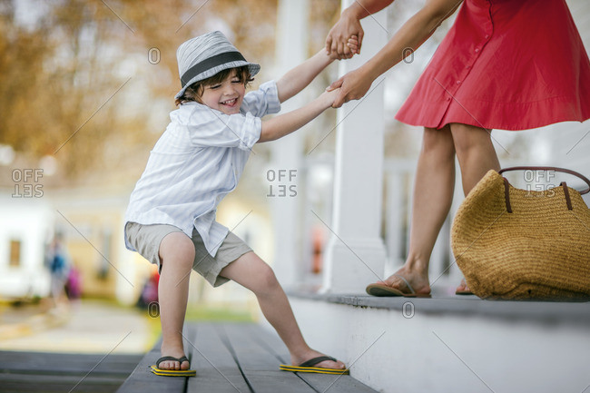 Impatient young boy hurrying his mother to leave the house for a vacation.