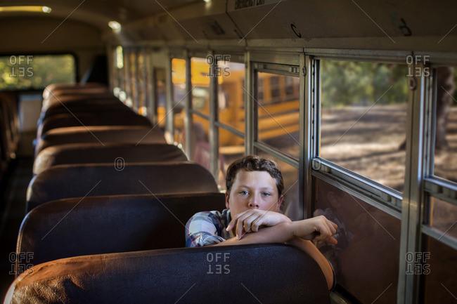 Young boy alone on a school bus.