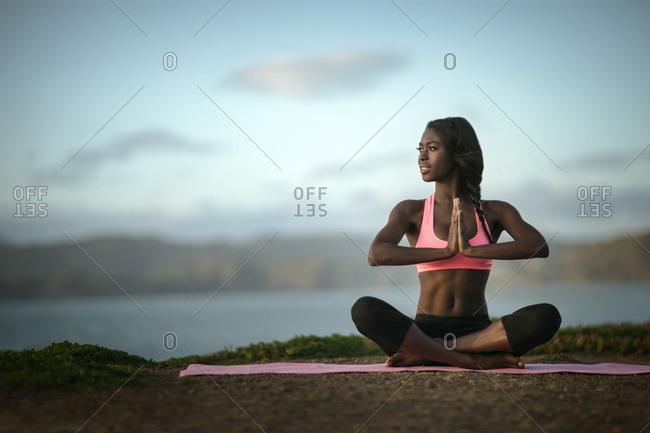 Young woman practising yoga by the ocean.