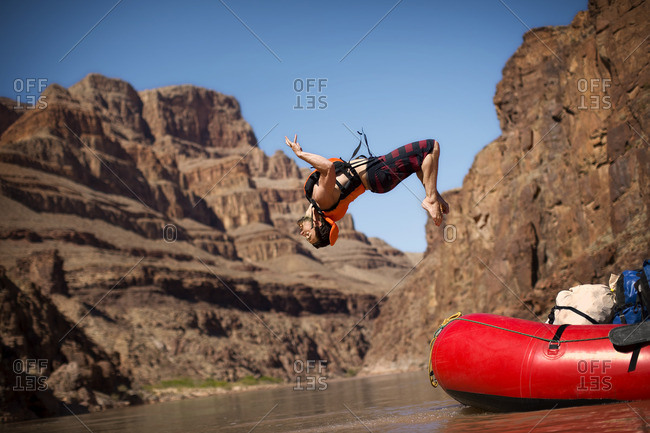 Young man back flipping into a river canyon from a dinghy.
