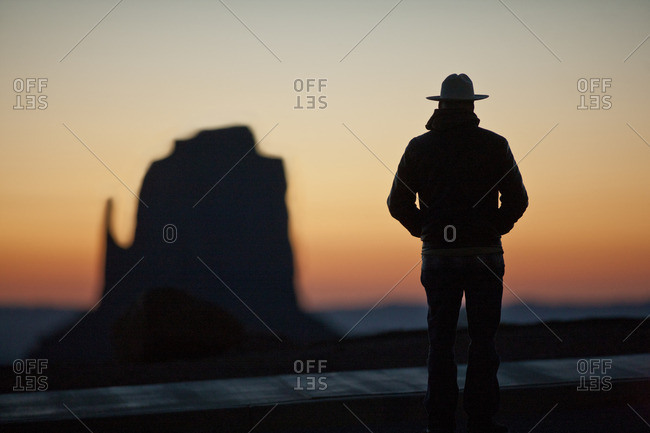 Man in cowboy hat admiring the Mitten rock formation at sunset, in Monument Valley Tribal Park in Arizona, USA.