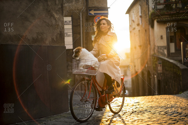 Young woman cycling on a cobblestone street, with her dog in the bicycle basket.