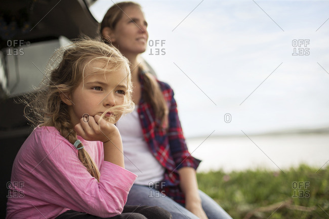 Mother and daughter sitting by a lake.