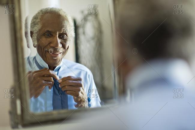Senior man tying his tie in the mirror.