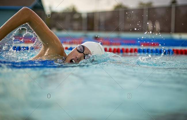 Young woman swimming the front crawl in a pool.