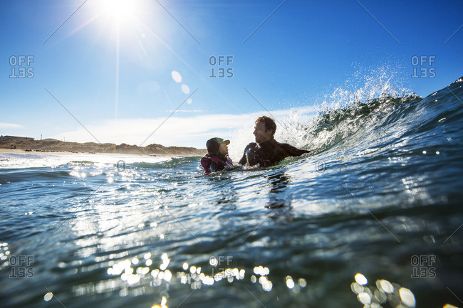 Father and daughter swimming in ocean waves.