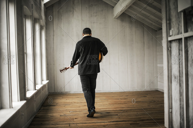 Man playing guitar in an empty room.