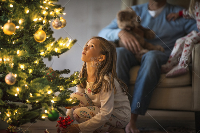 Father and daughters sitting around the Christmas tree.
