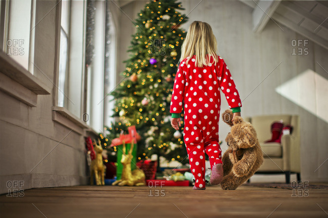 Young girl walking towards a Christmas tree with her teddy bear.