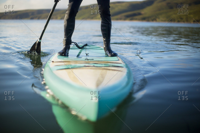 Paddle boarder on a calm lake.