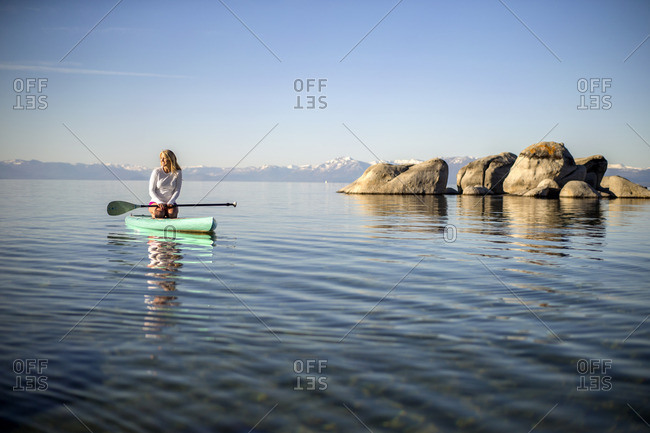 Young woman paddle boarding on a calm lake.