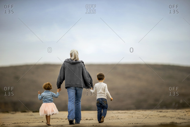 Grandmother walking with her two grandchildren on the beach.