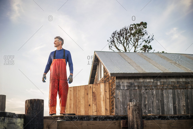 Fisherman in waders standing on a wooden pier.