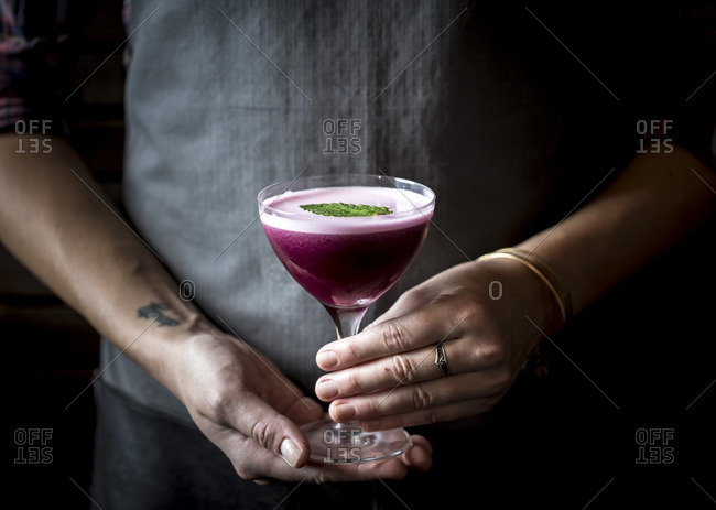 A woman holding a blueberry cocktail in a coupe glass
