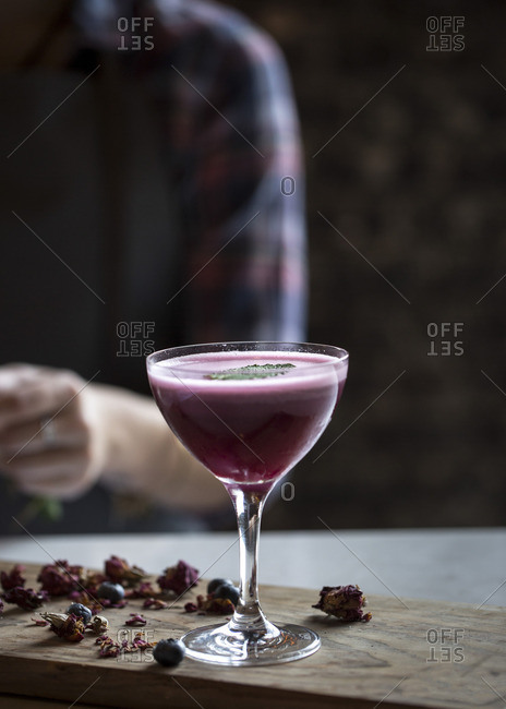 A coupe glass with a blueberry cocktail with the bartender in the background