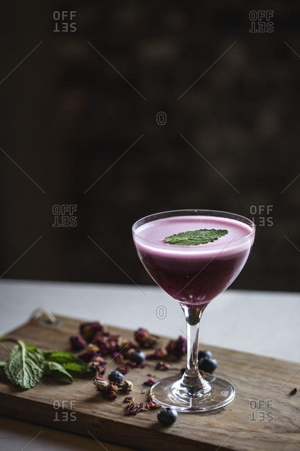 A coupe glass filled with a blueberry cocktail