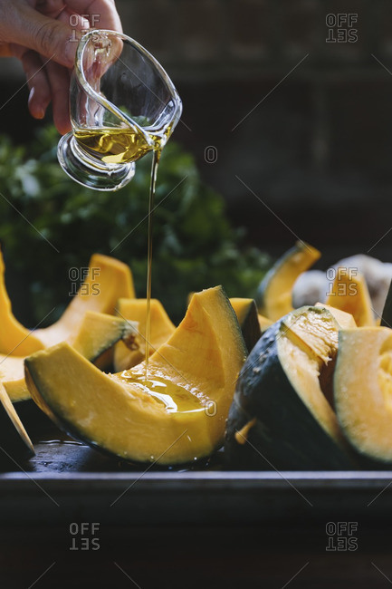 A woman is drizzling sliced kabocha squash with olive oil