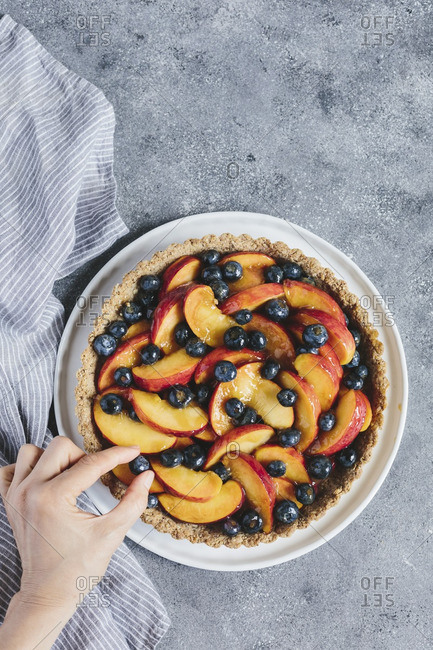 A woman is placing one last blueberry on a summer tart