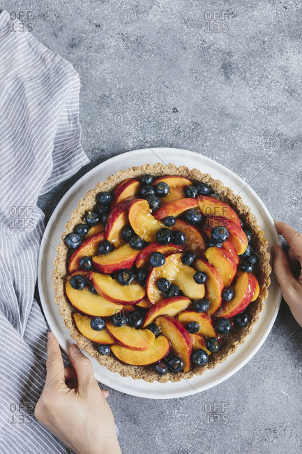 A woman is placing a peach and blueberry tart on to the table
