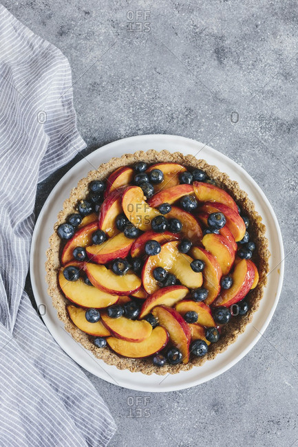 Overhead view of a fresh peach and blueberry tart