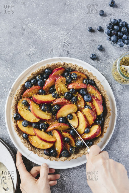 A woman slicing a peach and blueberry tart with a knife