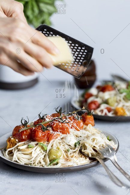 A woman shredding parmesan cheese onto a bowl of spaghetti topped off with roasted tomatoes, mozzarella cheese, and basil