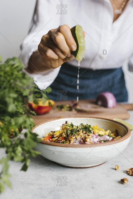 A woman squeezing lime into a bowl of peach and walnut salsa