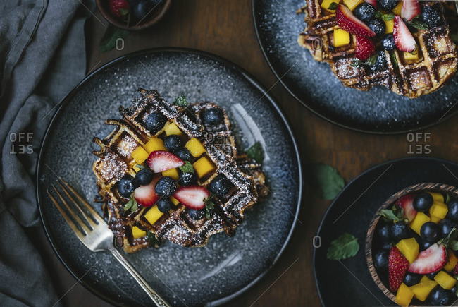 Overhead view of plates of brioche waffles topped with fruit and powdered sugar