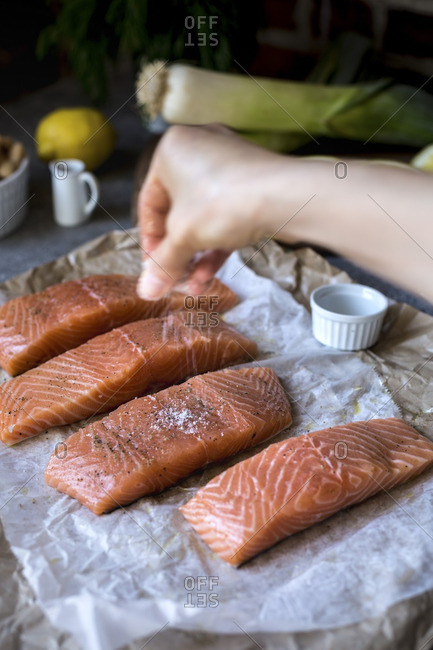 A woman seasoning fresh salmon with salt and pepper