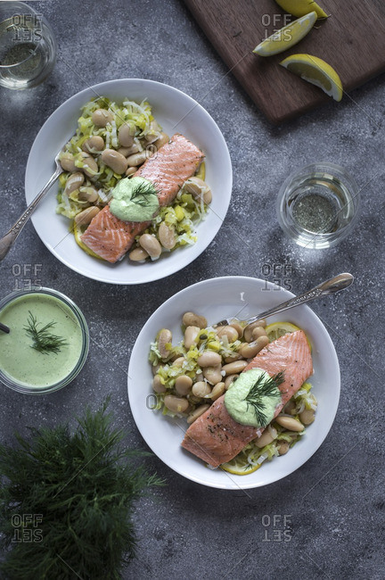 Two portions of slow baked salmon with butter beans served wine