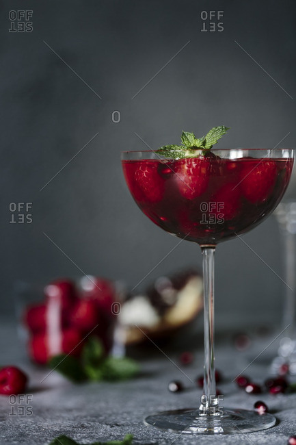 A coupe glass of raspberry and pomegranate champagne cocktail garnished with mint