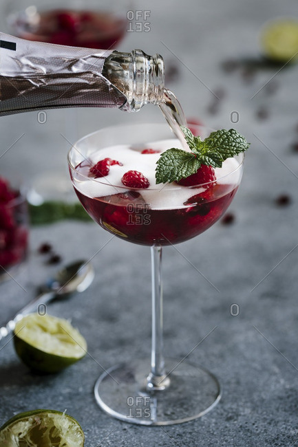 A glass of raspberry and pomegranate champagne cocktail being topped of with champagne