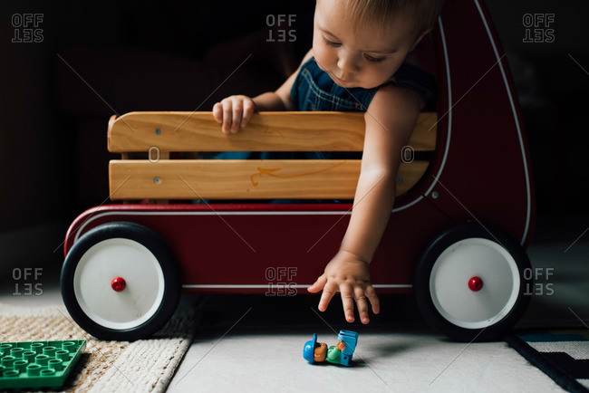 Baby in wagon reaching for a toy