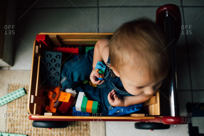 Baby sitting in wagon with toys