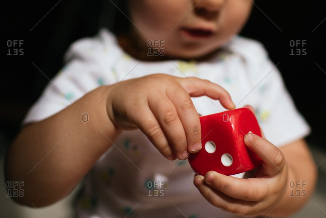 Baby's hands holding dice